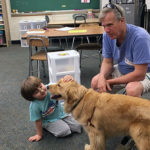 Boy from Uwchlan Hills Elementary School pets a dog