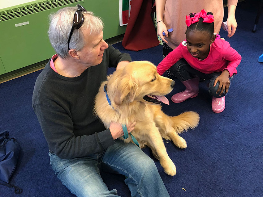 girl petting dog during school visit